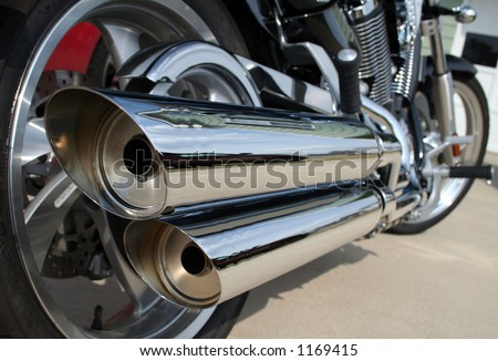 A rear view of a motorcycle with the focus on the chrome exhaust.