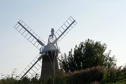 A rear view of a windmill (wind pump): tall traditional countryside building, surrounded by trees and bushes