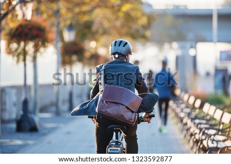 A rear view of businessman commuter with electric bicycle traveling to work in city.