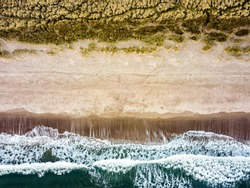 A receding ocean is seen from above from drone looking straight down. Waves leave beach with white froth lines in sea and strips of white and dark sand. Tidal details as ocean goes out with copy space