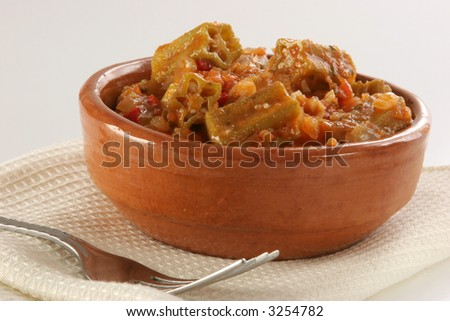 A recipe of okras (gumbos, Bamias) in mediterranean tomato's sauce with garlic, onion, chili, etc. with fork and napkin