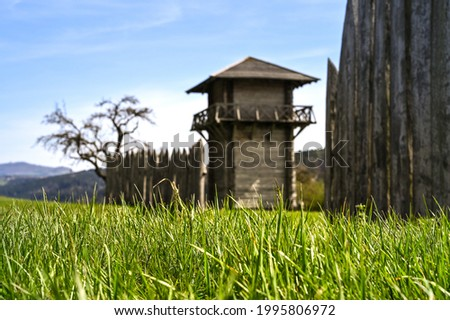 A reconstructed wooden Roman watchtower and a wooden border fence under a clear blue sky. This fortification was part of the 'Limes', the border of the former Roman Empire. Photo stock ©