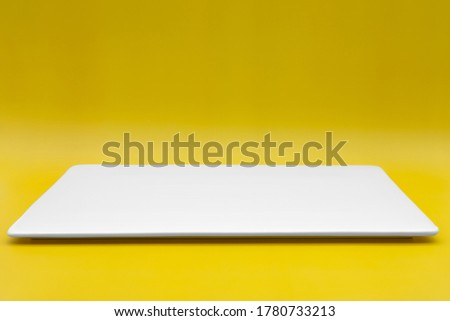 Photo of  A rectangle empty white plate isolated on the yellow background.