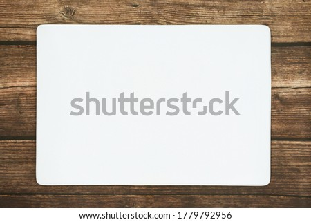 Photo of  A rectangle empty white plate on the rustic wooden floor.