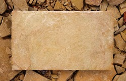 A rectangular slab of light sandstone against the background of stone fragments as the framework for your text. Light stone plate with copy space for text.