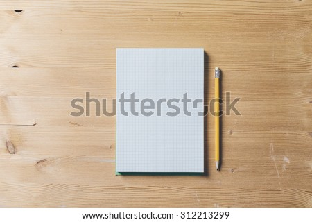 A recycled paper notebook checked with a black pencil with the eraser at the top, are arranged on a brown wooden table. View from the top
