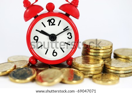 A red alarm clock on top of  Golden contents of coins signifying time and investments go together. - stock photo