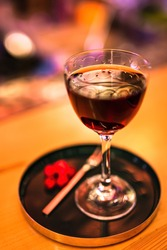 A red alcoholic cocktail in a nick and nora glass served on a tray with cranberry garnish. A lifestyle photo with shallow depth of field.
