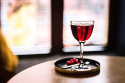 A red alcoholic cocktail in a nick and nora glass served on a tray with cranberry garnish, shot with back light. A lifestyle horizontal photo with shallow depth of field.
