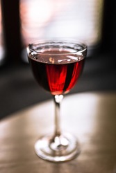 A red alcoholic cocktail in a nick and nora glass, shot with back light. A lifestyle vertical photo with shallow depth of field.