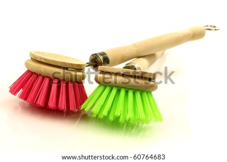a red and green dish washing brush on a white background
