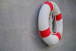 A red and white lifesaver with rope, hanging on a wall by a pool  for safety to rescue drowning swimmers.
