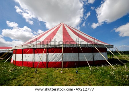 A red and white striped circus tent in green nature. The sky is blue with white cumulus clouds - stock photo