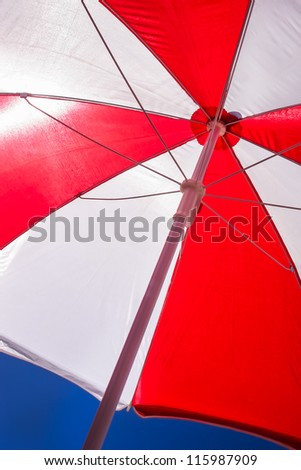 A red and white umbrella on the beach in clear skies.