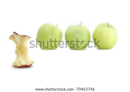 A red apple is singled out and eaten for being different to its green counterparts. Could be used to illustrate a variety of concepts. Isolated on a white background.