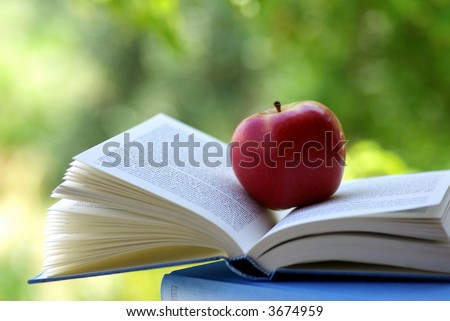 A red apple on a book of blue color.