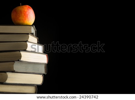A red apple on a books. Isolated over black background - stock photo