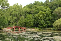 A red arched bridge over a lake leading to walking trails through a forest and around the lake at Rotary Botanic Gardens in Janesville, Wisconsin, USA