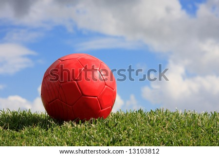 A red ball on a playing field with a cloudy sky
