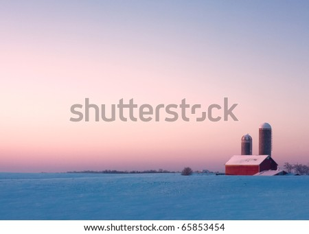 A red barn and silos surrounded by snow on an early winter morning.