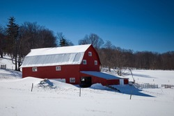 A red barn in Canaan Valley West Virginia surrounded by snow under a clear blue sky