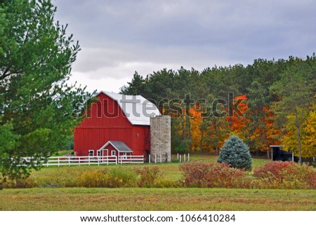 A red barn with a roofless stone silo stands in front of a piney woods. A neat white fence encircles the barnyard. A few deciduous trees and the surrounding vegetation display seasonal fall color. #1066410284