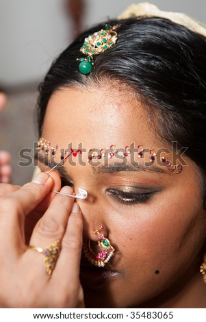 A Red Bindi is applied to a Hindu brides forehead