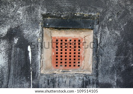 A red brick air grate in a black rendered wall