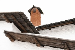 A red brick chimney rises above the chaotic crosshairs of three wooden roofs in the Pskov Kremlin.
