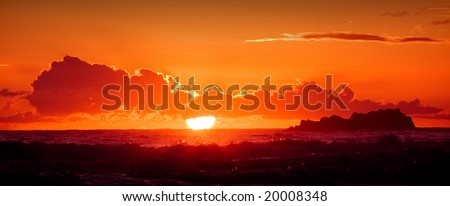 A red burning sunset with the silhouett of an island over a stormy ocean