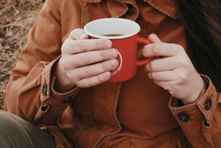 A red camping mug with coffee in the hands of a girl in a brown parka jacket.
