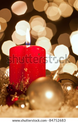 a red candle with christmas balls in atmospheric light with bokeh