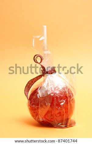 A red candy apple in a plastic wrapper ready for treating the sweet tooth.