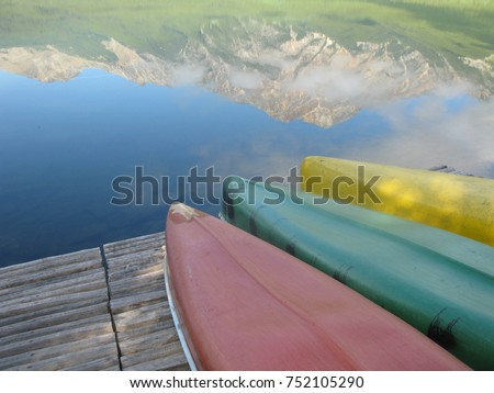 A red canoe, a green canoe, and a yellow canoe upturned on a wood boat dock in a lake, with the reflection of a snow-capped mountain, in the  Canadian Rockies, British Colombia, Canada. Room for text.