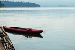 A red canoe (kayak) floating on the water during the evening in Khao Sok National Park lake in Thailand. This photo can be used to as recreation background image.
