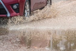 A red car speeding through the sewage road splashing yellow water splash