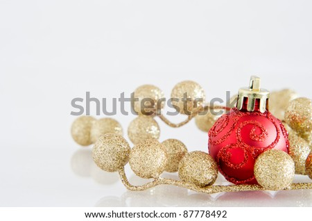 A red Christmas bauble with glittery spiral pattern and gold glitter ball decorations on an off-white reflective surface with copy space above and to left.
