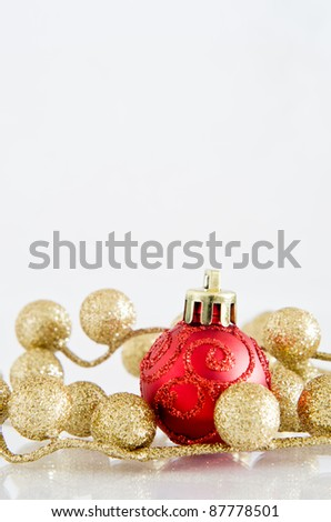 A red Christmas bauble with glittery spiral pattern and gold glitter ball decorations on an off-white reflective surface with copy space above.