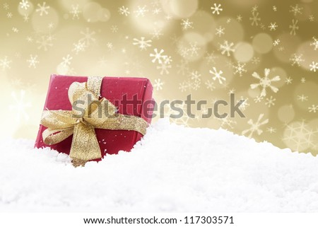 A red christmas gift with golden defocused lights background