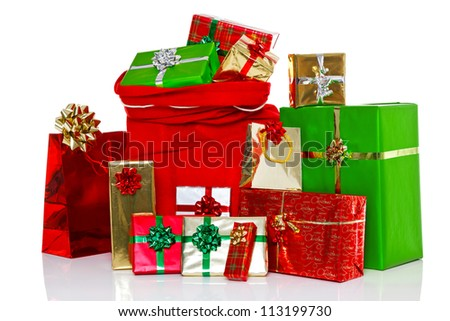 A red Christmas sack full of and surrounded by gift wrapped presents, isolated on a white background.