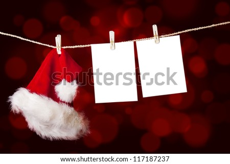 A red christmas Santa hat is hanging on a string together with notes on defocused red lights