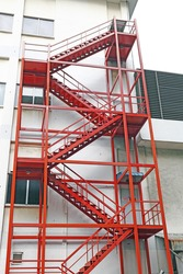 A red color fire escape ladder on the side of a building.