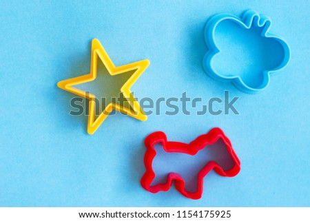 A red cow-shaped, butterfly-shaped, and star-shaped cookie or biscuit cutter placed over a blue background. The tools are used for cutting cookie dough into a particular shape.