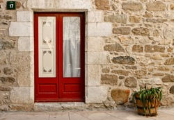 a red door in a stone house, wall and a flowerpot