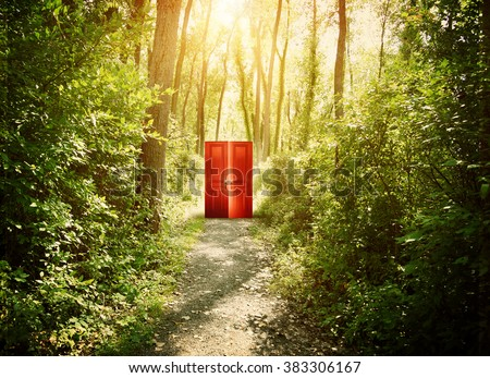 A red doorway is on a trail in the woods with trees for a conceptual concept about faith, freedom or freedom concept.