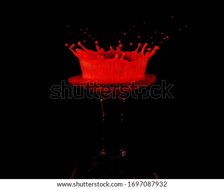 A red drop of milk splashed onto an upturned miniature wine glass creates a crown shaped splat against a black background