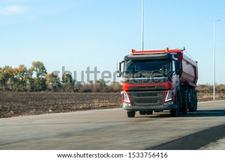 A red dump truck drives out of town on a flat asphalt road among fields against a blue sky on a sunny day. A machine for transporting building materials rides on the highway #1533756416
