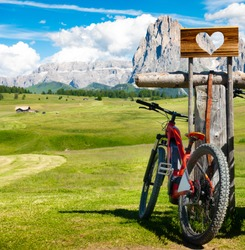 A red e-bike (ebike electric mountain bike) on a wonderful panorama with tracks, grass and mountains in Seiser Alm, Alpe di Siusi, Val Gardena