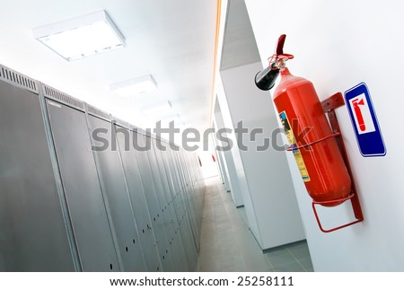 a red fire-extinguisher hangs on a white wall in an apartment
