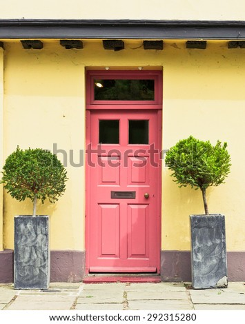 A red front door in a yellow cottage in England